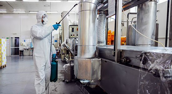 Man in protective suit and mask disinfecting machine facilities